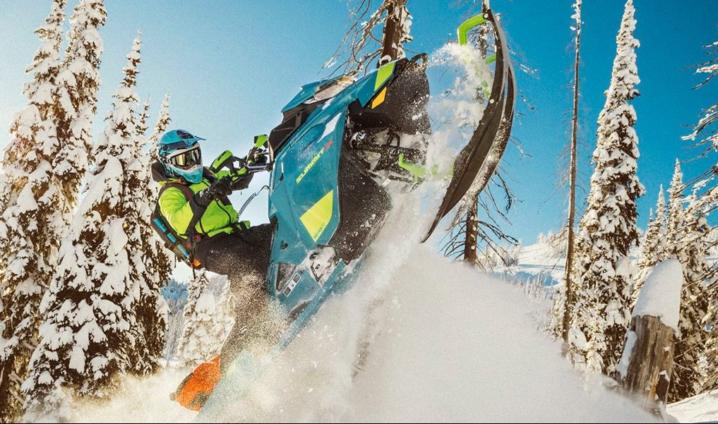 A man riding on a snowmobile in fresh powder